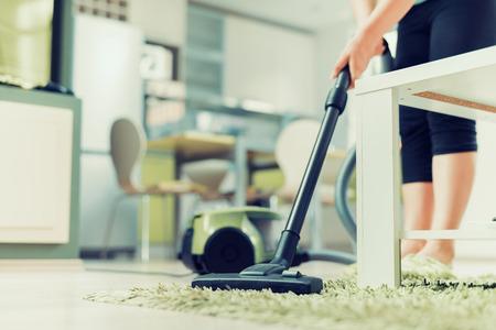 Close-up van de vrouw met de benen stofzuiger schoonmaken tapijt thuis.