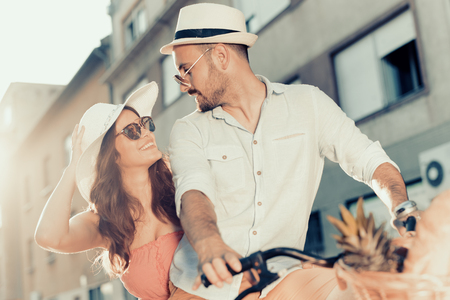 Happy young couple going for a bike ride in the city. Stockfoto
