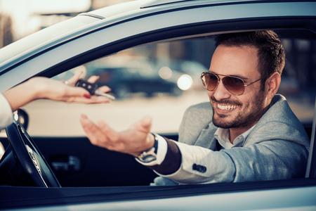 Car dealership.Young man receiving car key from saleswoman.