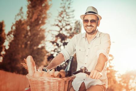 Gelukkig jonge man is het rijden van de fiets in het park.
