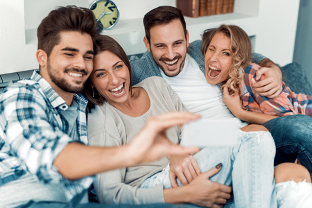 Cheerful group of friends having fun at home,taking selfie. Stockfoto