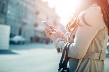 Jeune femme marchant et en utilisant un téléphone intelligent dans une rue de la ville. Banque d'images