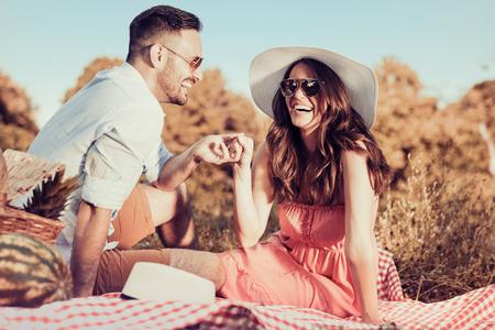 Jeune couple ayant un pique-nique dans le parc sur une journée ensoleillée.