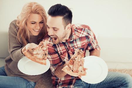 Couple de manger la pizza collation à la maison.