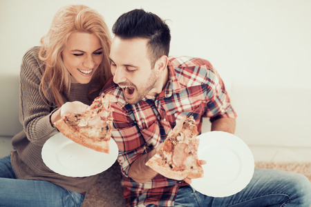 Couple eating pizza snack at home. Stockfoto