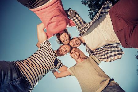 cercle d'amis heureux étreignant ensemble au parc, avoir du plaisir ensemble.