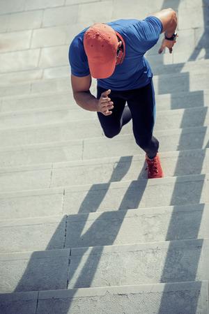 Gros plan d'un jeune homme en cours d'exécution dans les escaliers. Banque d'images