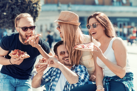 Friends eating pizza.They are enjoying together,eating pizza and having fun.