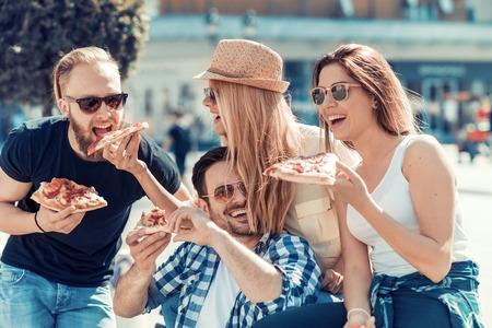 Vrienden die pizza eten. Ze genieten samen, eten pizza en hebben plezier.