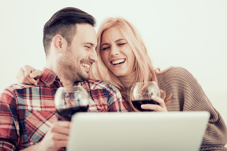 Young couple celebrating with red wine at home,enjoying together at home.Spending nice time at home.