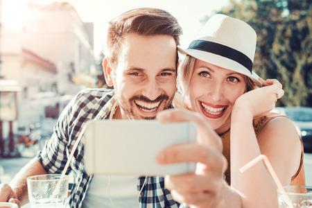 Jeune couple de prendre une photo d'eux-mêmes dans un café.