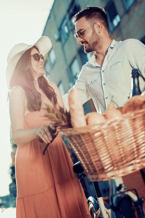 Jeune couple ayant du plaisir dans le jeune couple city.Happy aller pour une balade à vélo dans la ville.