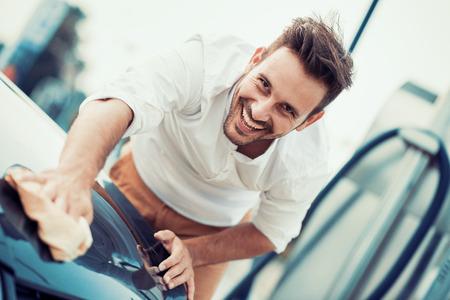 Man ouvrier polissage voiture sur un lavage de voiture à l'extérieur.