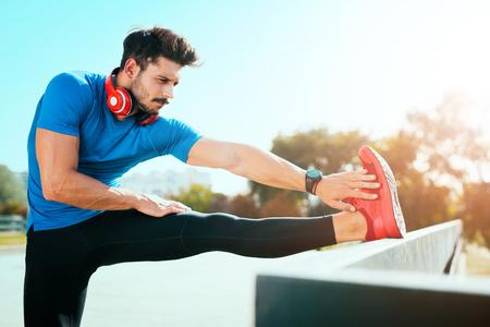 coureur Homme étirement exercice, la préparation pour l'entraînement du matin dans le park.Fitness et le concept de style de vie.