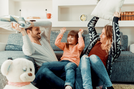 Happy family playing with daughter in the living room.