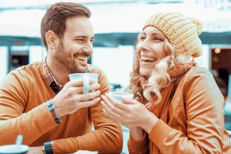 Jeune couple se amuser tout en étant assis ensemble dans un café de la ville