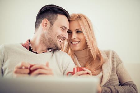 Young couple browsing internet at home,using laptop and smiling.