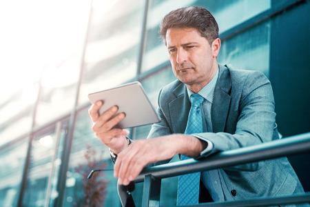 Close up portrait of a successful businessman using a digital tablet outdoors. Banque d'images