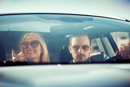 Enjoying road trip together.Happy young couple having fun while riding in their car. Фото со стока
