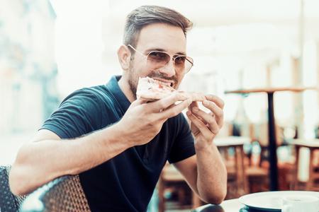 男子吃比薩餅快餐戶外。