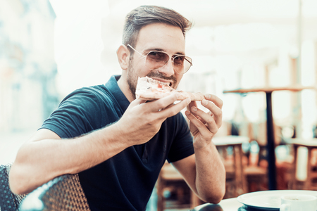 Man eating pizza snack outdoors.