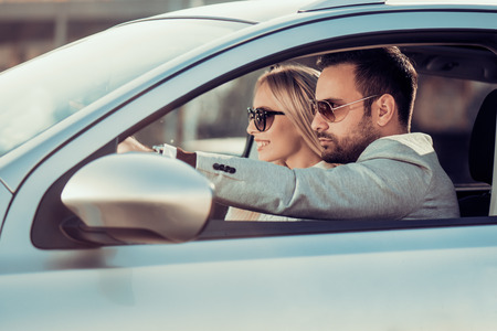 Disfrutando de viaje por carretera together.Happy joven pareja que se divierten mientras que monta en su coche. Foto de archivo