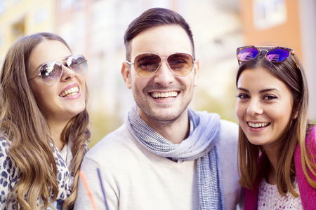 Group of happy friends laughing and taking a selfie in the city.