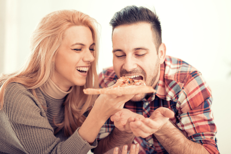 Couple eating pizza snack at home. Banque d'images
