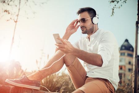 Junge attraktive Mann lächelt, während Kopfhörer tragen.