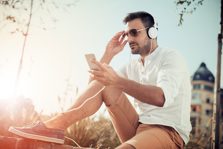 Young attractive man is smiling while wearing headphones. 版權商用圖片
