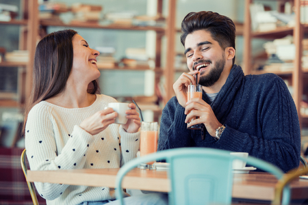 Young couple sitting in cafe by a window and laughing.They are enjoying together and having a great time. Stockfoto