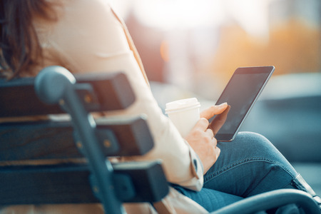 Woman use break at work to drink coffee and use digital tablet.