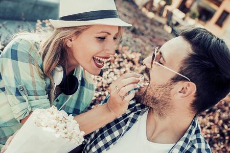 Gelukkig jong koppel zittend op een bankje bij elkaar en het eten van popcorn, plezier samen.