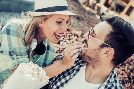 Happy young couple sitting on a bench together and eating popcorn,having fun together.