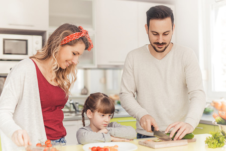 Happy family preparing vegetables together at home in the kitchen. Stockfoto