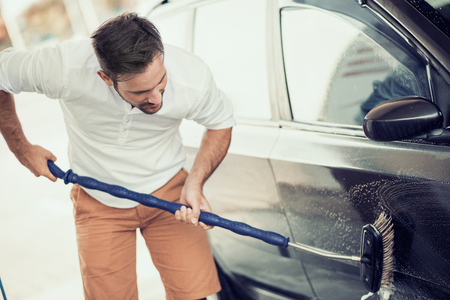 Young man cleaning his car outdoors. Banco de Imagens