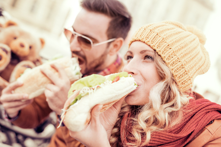 Happy young couple.They are eating sandwich and having a great time. Stockfoto
