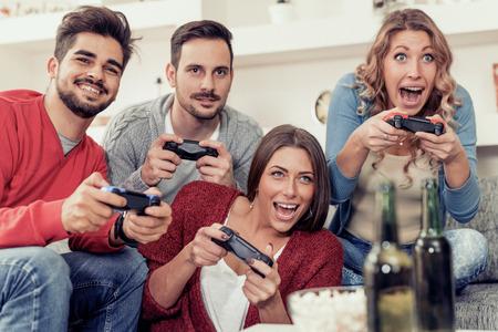 Grupo de amigos que se inclinan hacia un lado mientras juegan juegos de video juntos.