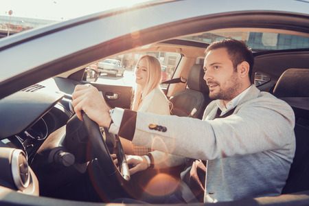 道路の旅を一緒に楽しんでいます。自分の車に乗りながら楽しんで幸せな若いカップル。 写真素材