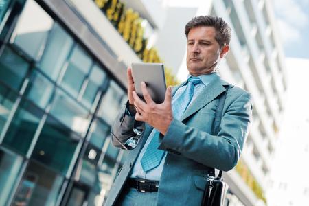 Feche acima do retrato de um homem de negócios bem sucedido usando uma tabuleta digital ao ar livre.