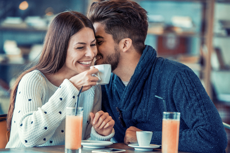 Young couple sitting in cafe by a window and laughing.They are enjoying together and having a great time. Banco de Imagens