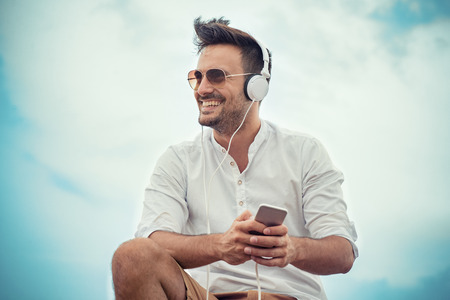 而戴著耳機的年輕人有吸引力的人在微笑。 版權商用圖片