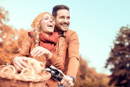 夫婦愉快的年輕人去為晴天在公園裡騎自行車。 版權商用圖片