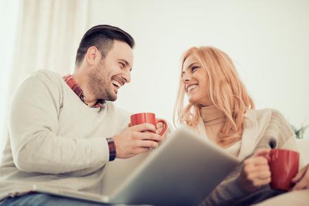 Jong paar surfen op internet thuis, met behulp van laptop en smiling.They samen te genieten en een geweldige tijd.