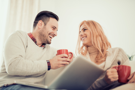 Young couple browsing internet at home,using laptop and smiling.They are enjoying together and having a great time.