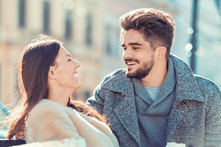 Happy young couple hugging and laughing outdoors. Banco de Imagens