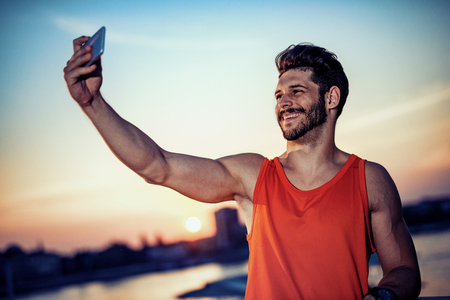 Attractive man making a selfie after exercise.