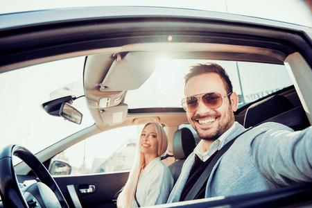 Bénéficiant voyage sur la route together.Happy jeune couple ayant du plaisir tout en équitation dans leur voiture.