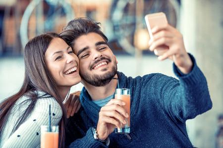 年輕的情侶走自己的照片在咖啡館。
