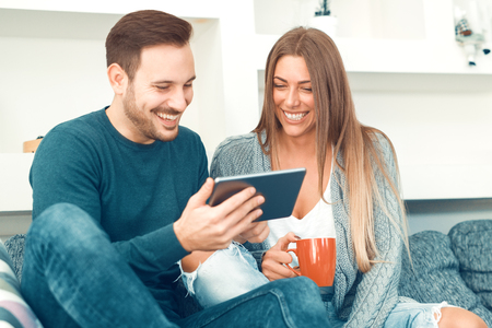 Loving young couple sitting on the couch at home,using digital tablet.